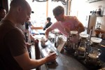 Four Barrel's slow bar barista hands two men their hand-brewed cups coffee in the morning.